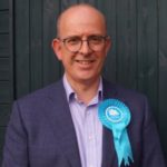 Andy Coles wearing a Conservative Party rosette