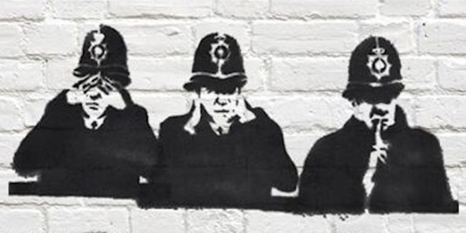 Spraypain stencil of 3 British police in 'brass monkeys' pose